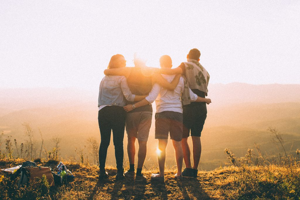 Friends hiking together with sunset in the background. Blog Banner.
