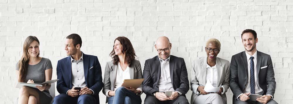 Colleagues smiling and talking, sitting shoulder to shoulder