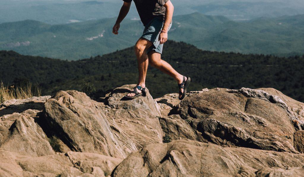 man hiking, walking over rocky terrain