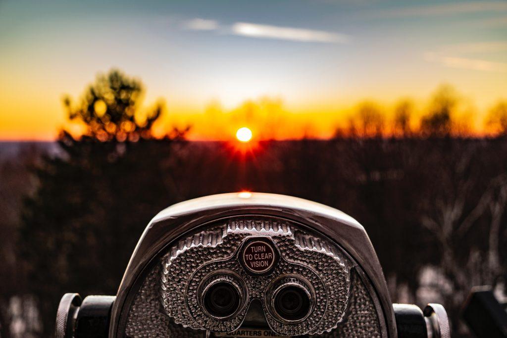 telescope overlooking a sunset landscape